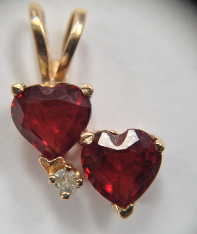 14K YELLOW GOLD-STONE PENDANT WITH TWO RED STONE HEARTS AND SMALL WHITE STONE.