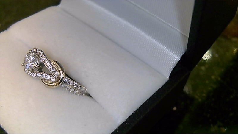 Lady's 14k white gold 1/3ct round with side round diamonds in a knot style ring