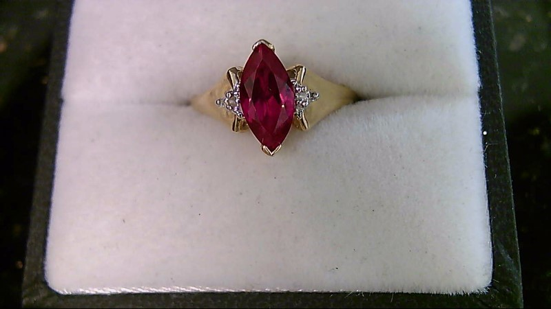 Lady's 10k yellow gold synthetic marquise ruby with 2- round cubic zirconia ring