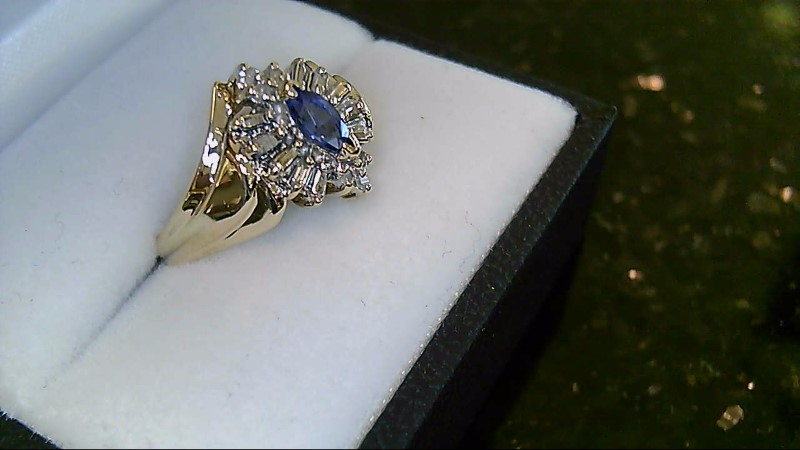 Lady's 10k yellow gold marquise tanzanite with round and baguette diamond ring