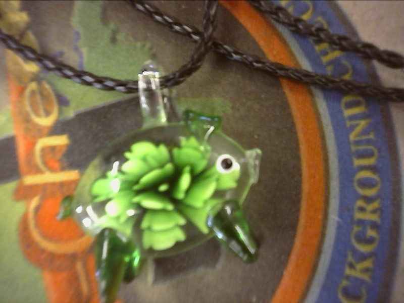 GLASS PIG WITH GREEN FLOWERS INSIDE PENDANT ON BLACK BRAIDED CORD