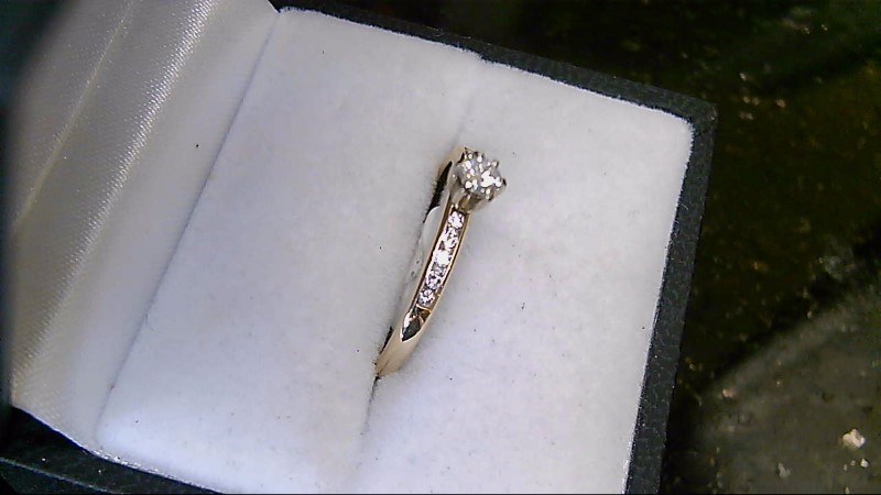 lady's 14k yellow gold ring with round center and round side diamons